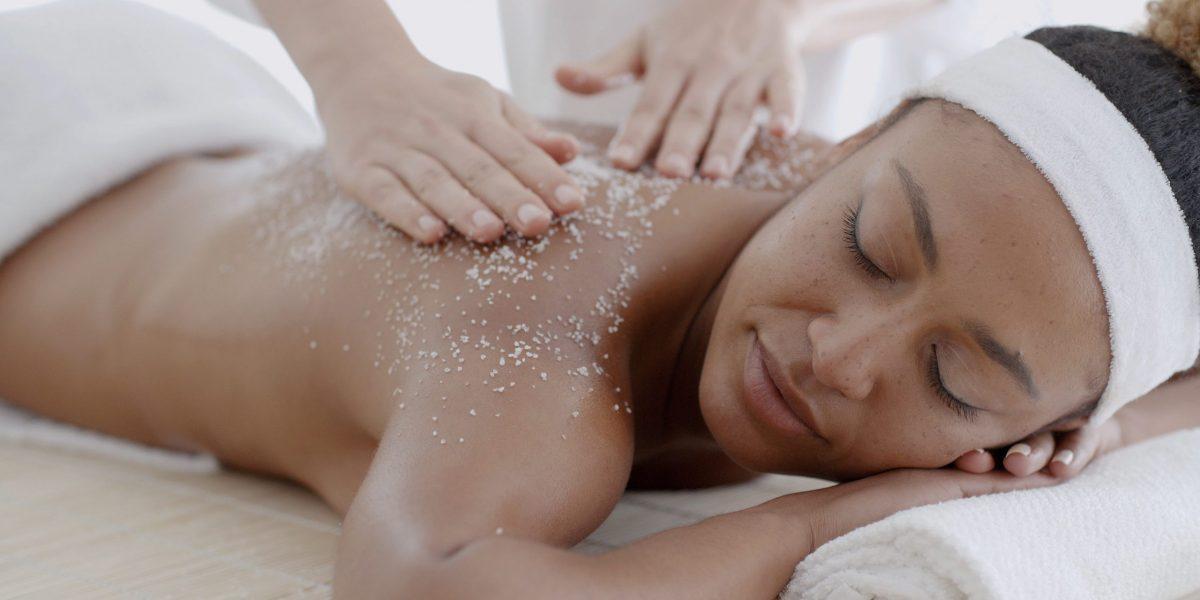 Female getting a salt scrub beauty treatment in the health spa
